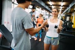 Mujer hermosa joven que hace ejercicios con el instructor personal imagen de archivo libre de regalías
