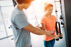 Mujer hermosa joven que hace ejercicios con el instructor personal imágenes de archivo libres de regalías
