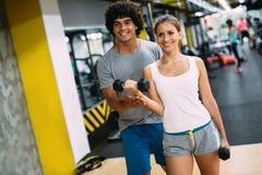 Mujer hermosa joven que hace ejercicios con el instructor personal fotos de archivo libres de regalías