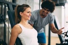 Mujer hermosa joven que hace ejercicios con el instructor personal fotos de archivo