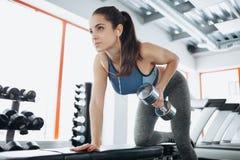 Mujer hermosa joven que hace ejercicios con pesa de gimnasia en gimnasio fotos de archivo libres de regalías