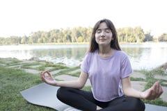 Mujer hermosa joven que hace ejercicios de la yoga en parque en el río del banco fotos de archivo
