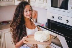 Mujer hermosa joven que hace la torta en la cocina Fotos de archivo