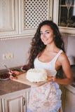 Mujer hermosa joven que hace la torta en la cocina Foto de archivo