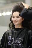 Mujer hermosa joven que hace un otoño muy de moda de Intercharm Moscú del peinado Fotos de archivo