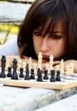 Mujer hermosa joven que juega a ajedrez Foto de archivo