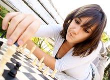 Mujer hermosa joven que juega a ajedrez Imagen de archivo