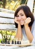 Mujer hermosa joven que juega a ajedrez Foto de archivo libre de regalías
