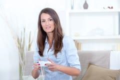 Mujer hermosa joven que juega al videojuego Imagen de archivo