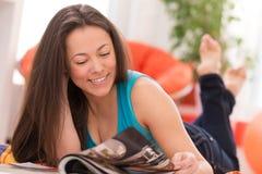 Mujer hermosa joven que lee en casa Fotos de archivo libres de regalías