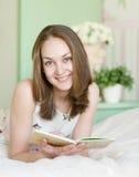 Mujer hermosa joven que lee un libro Imagen de archivo libre de regalías