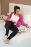 Mujer hermosa joven que lee un libro con el ordenador portátil en dormitorio Imagen de archivo libre de regalías