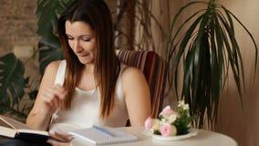 Mujer hermosa joven que lee un libro y que toma notas Mujer que lee un libro que se sienta en una silla almacen de metraje de vídeo