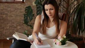 Mujer hermosa joven que lee un libro y que toma notas Mujer que lee un libro que se sienta en una silla almacen de video