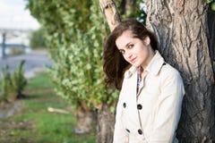 Mujer hermosa joven que lleva la chaqueta beige que se coloca sobre el árbol Foto de archivo libre de regalías