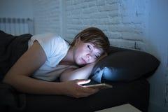 Mujer hermosa joven que miente en caer de la cama dormido usando el teléfono elegante tarde en la noche en un dormitorio oscuro imagen de archivo libre de regalías