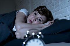 Mujer hermosa joven que miente en cama tarde en la noche que sufre del insomnio que intenta dormir fotos de archivo