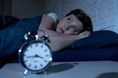 Mujer hermosa joven que miente en cama tarde en la noche que sufre del insomnio que intenta dormir foto de archivo