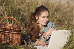 Mujer hermosa joven que miente en campo en la computadora portátil foto de archivo
