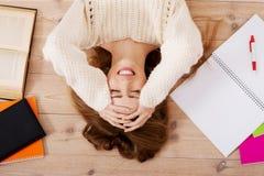 Mujer hermosa joven que miente en el piso con los libros. Fotos de archivo