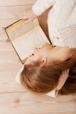 Mujer hermosa joven que miente en el piso con los libros. Fotografía de archivo