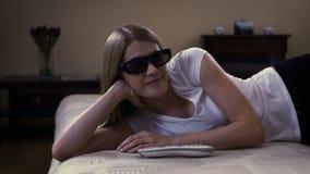 Mujer hermosa joven que miente en el sofá Pone los interruptores 3d-glasses en la TV elegante y mira la película 3d almacen de video