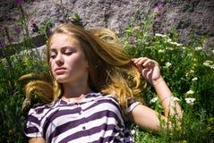 Mujer hermosa joven que miente en hierba larga Foto de archivo libre de regalías
