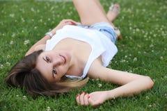 Mujer hermosa, joven que miente en hierba verde Fotos de archivo libres de regalías