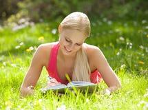 Mujer hermosa joven que miente en la escritura de la hierba en diario Foto de archivo
