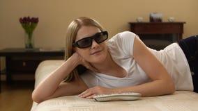 Mujer hermosa joven que miente en un sofá Pone los interruptores 3d-glasses en la TV elegante y mira la película 3d almacen de video