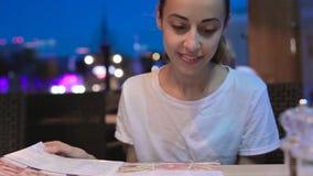 Mujer hermosa joven que mira el menú en restaurante, páginas de torneado y eligiendo las placas para la datación del acontecimien almacen de metraje de vídeo