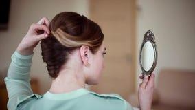Mujer hermosa joven que mira en el espejo almacen de metraje de vídeo