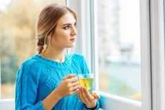 Mujer hermosa joven que mira hacia fuera la ventana y que bebe té T Foto de archivo libre de regalías