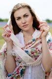 Mujer hermosa joven que mira la cámara que se coloca en campo de trigo amarillo en mantón Fotografía de archivo libre de regalías