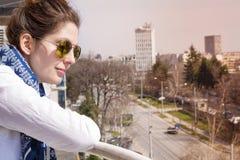 Mujer hermosa joven que mira la calle de un balcón Imagen de archivo libre de regalías