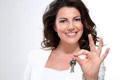 Mujer hermosa joven que muestra claves del apartamento Imagenes de archivo