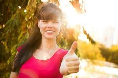 Mujer hermosa joven que muestra los pulgares encima de o como Foto de archivo libre de regalías