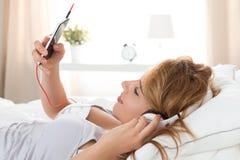 Mujer hermosa joven que pone en su dormitorio y que escucha el mus Imagen de archivo libre de regalías