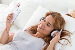 Mujer hermosa joven que pone en su dormitorio y que escucha el mus Fotos de archivo libres de regalías