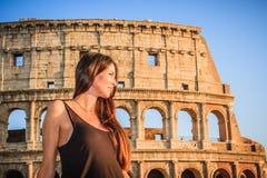Mujer hermosa joven que presenta delante del Colosseum Ruinas de mármol de los arcos sobre un cielo azul, Roma, Italia fotografía de archivo libre de regalías