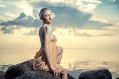 Mujer hermosa joven que presenta en la playa en la puesta del sol Imagenes de archivo