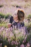 Mujer hermosa joven que presenta en un campo de la lavanda Fotografía de archivo