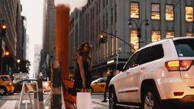 Mujer hermosa joven que se coloca adentro en el centro de la ciudad con el panier de Nueva York, América cerca del tubo del humo, almacen de video
