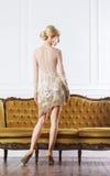 Mujer hermosa, joven que se coloca cerca de un sofá Imágenes de archivo libres de regalías