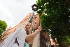 Mujer hermosa joven que se coloca con el teléfono móvil contra la perspectiva del edificio de ladrillo viejo Foto de archivo