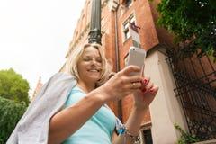 Mujer hermosa joven que se coloca con el teléfono móvil contra la perspectiva del edificio de ladrillo viejo Imagen de archivo
