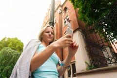 Mujer hermosa joven que se coloca con el teléfono móvil contra la perspectiva del edificio de ladrillo viejo Foto de archivo libre de regalías