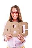 Mujer hermosa joven que se coloca con las letras de ABC Foto de archivo