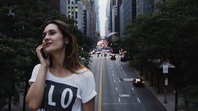 Mujer hermosa joven que se coloca en el centro de la ciudad del puente adentro de Nueva York, América y hablando en el teléfono m almacen de metraje de vídeo