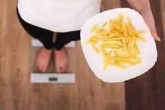 Mujer hermosa joven que se coloca en escalas y que sostiene las patatas fritas El concepto de consumición sana Forma de vida sana Imagen de archivo